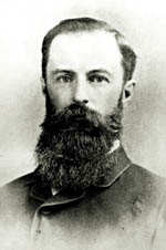 Black and white photo of Reginald Murray wearing a suit and a long, dark beard