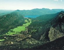 View of a green valley with mountains either side and a lake in the distance