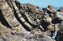 A grey rock face showing segments of rock broken up into thick layers