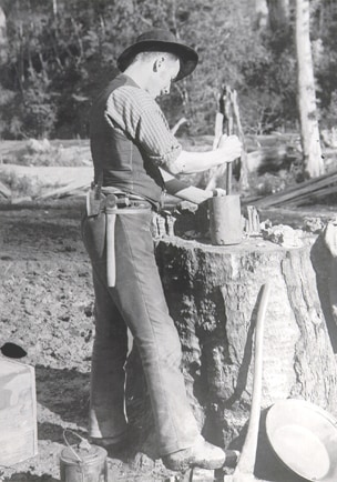 An old black and white photo of a miner crushing quartz in a pot.