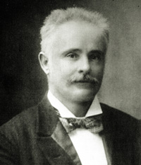 Black and white photo of James Stirling wearing a suit, bow tie and moustache